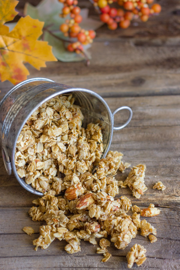 Pumpkin Pie Spice Coconut Oil Granola spilling out of a mini galvanized bucket, with fall decorations in the background.