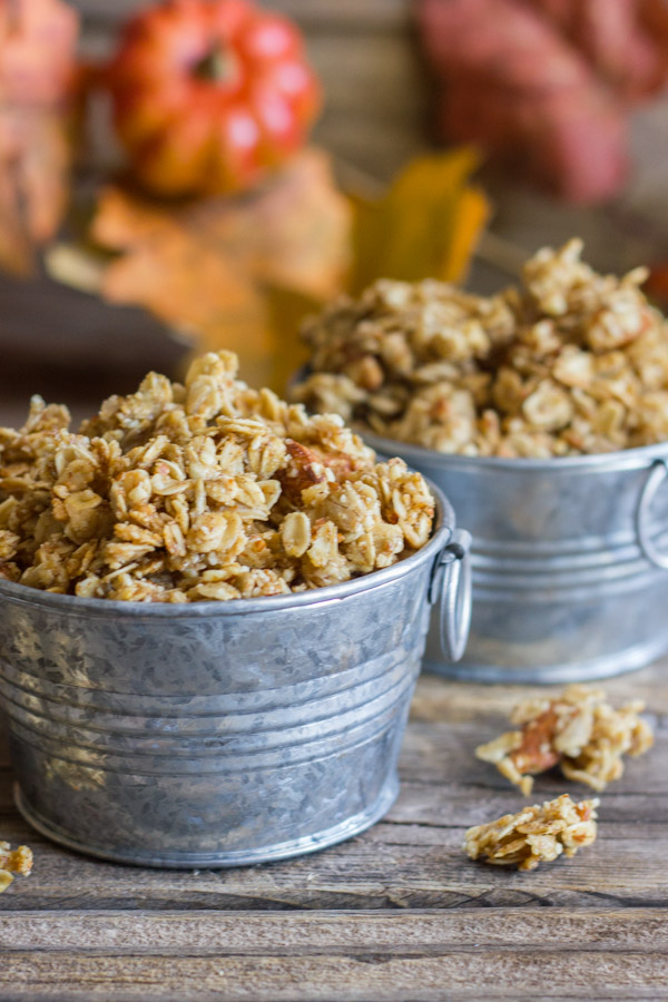 Pumpkin Pie Spice Coconut Oil Granola in two mini galvanized buckets, with some granola clusters next to the buckets and fall decorations in the background.