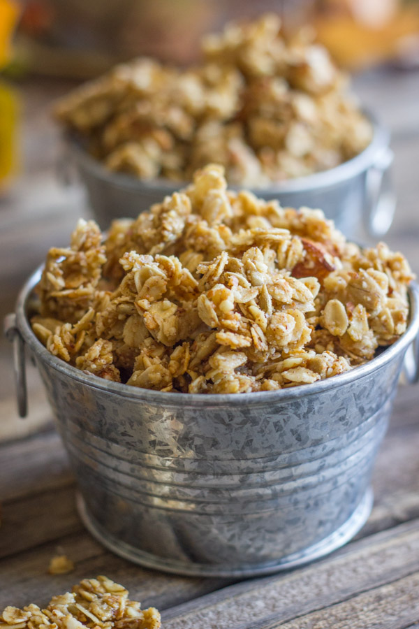 Pumpkin Pie Spice Coconut Oil Granola in two mini galvanized buckets, with some granola clusters next to the buckets.