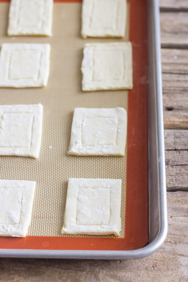 Puff pastry that has been cut and scored, arranged on a Silpat lined baking sheet.