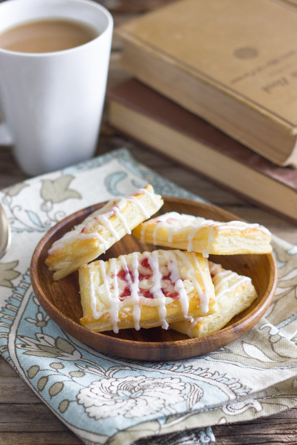 Raspberry Cream Cheese Danishes on a wood plate that is sitting on a cloth napkin, with a cup of coffee and stacked books in the background.