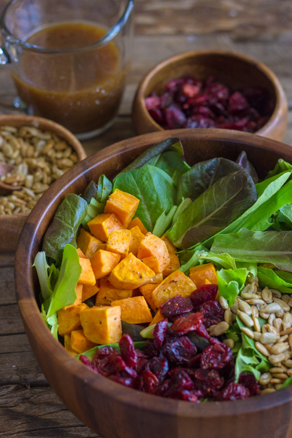 Roasted Sweet Potato Salad ingredients in a wood bowl, with two small bowls of sunflower seeds and dried cranberries, along with a small glass pitcher of dressing in the background.