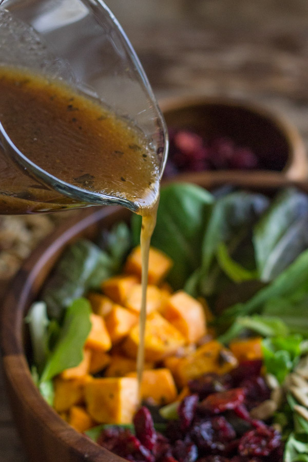 Salad dressing being poured over the Roasted Sweet Potato Salad.
