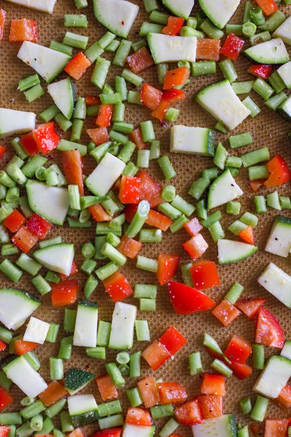Chopped vegetables for Vegetable Tortellini With Creamy Garlic Sauce on Silpat lined baking pan.