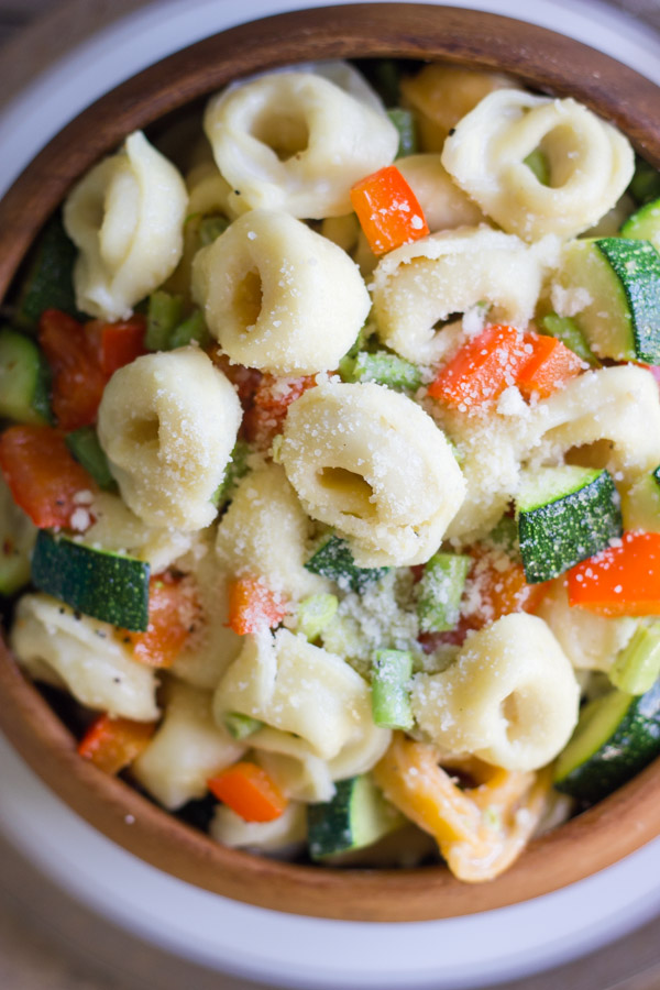 Vegetable Tortellini With Creamy Garlic Sauce in a wood bowl sitting on a plate.