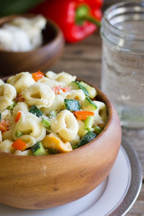 Vegetable Tortellini With Creamy Garlic Sauce in a wood bowl sitting on a plate, with a glass of water, a small wood bowl of garlic bulbs and a red pepper in the background.
