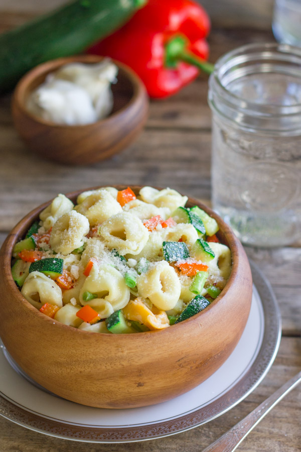 Vegetable Tortellini With Creamy Garlic Sauce in a wood bowl sitting on a plate, with a glass of water, a small wood bowl of garlic bulbs, a zucchini and a red pepper in the background.