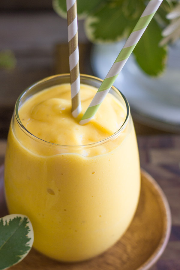 Tropical Sunshine Smoothie in a glass with two straws sitting on a little wood saucer.