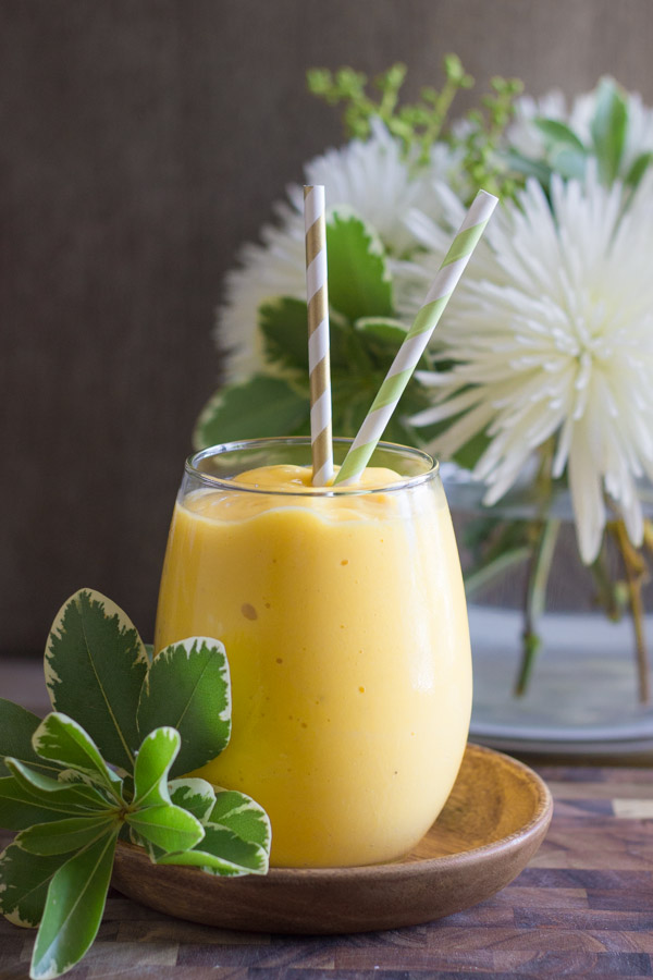 Tropical Sunshine Smoothie in a glass with two straws sitting on a little wood saucer, with a flower arrangement in the background.