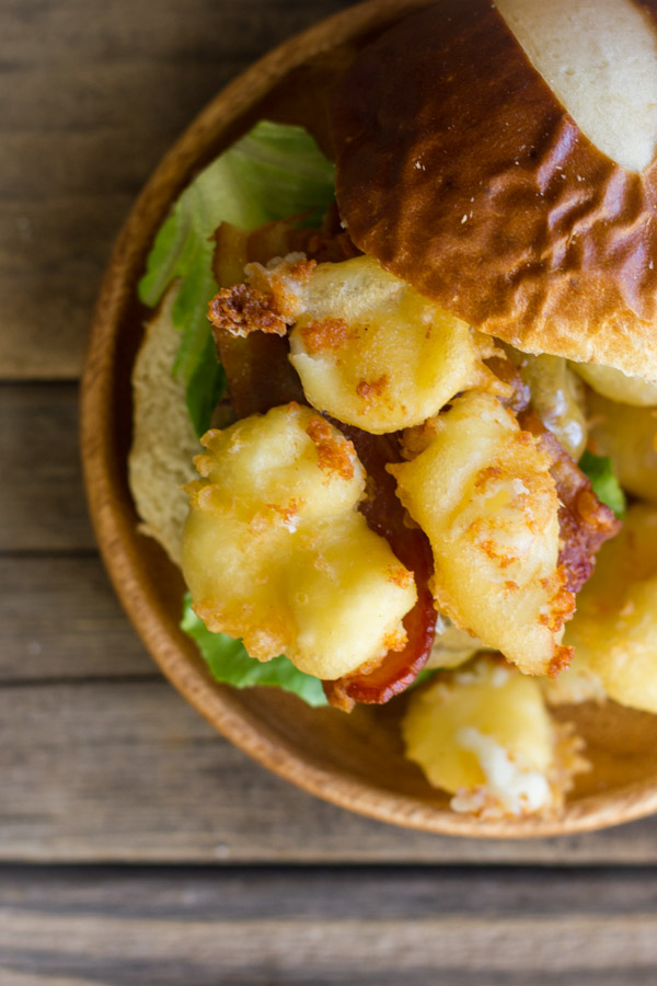Western Bacon Sliders With Fried Cheese Curds on a wood plate.