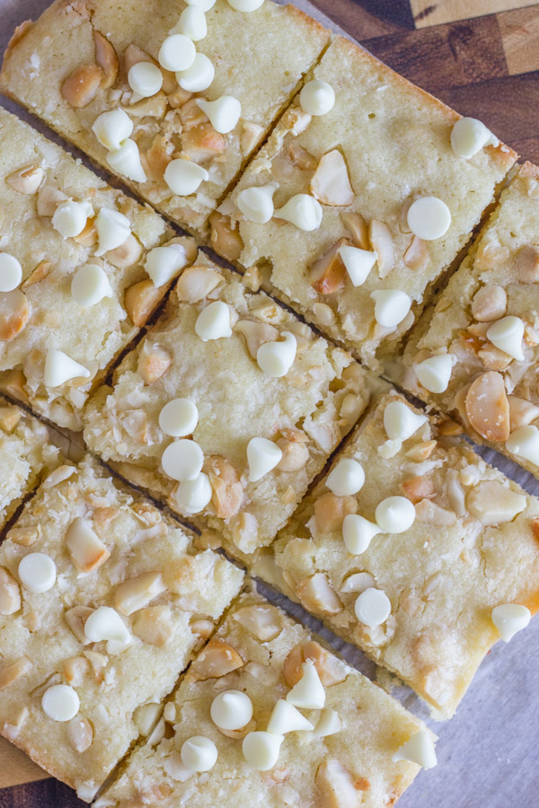 White Chocolate Macadamia Nut Bars cut into squares on a cutting board.