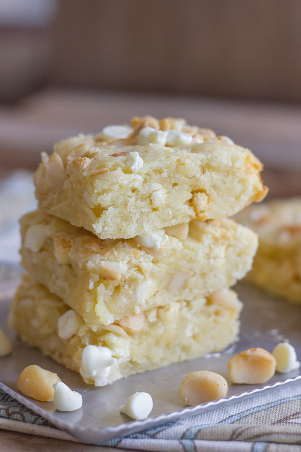 White Chocolate Macadamia Nut Bars stacked in a pile of three on a serving platter, with a few macadamia nuts and white chocolate chips around them.