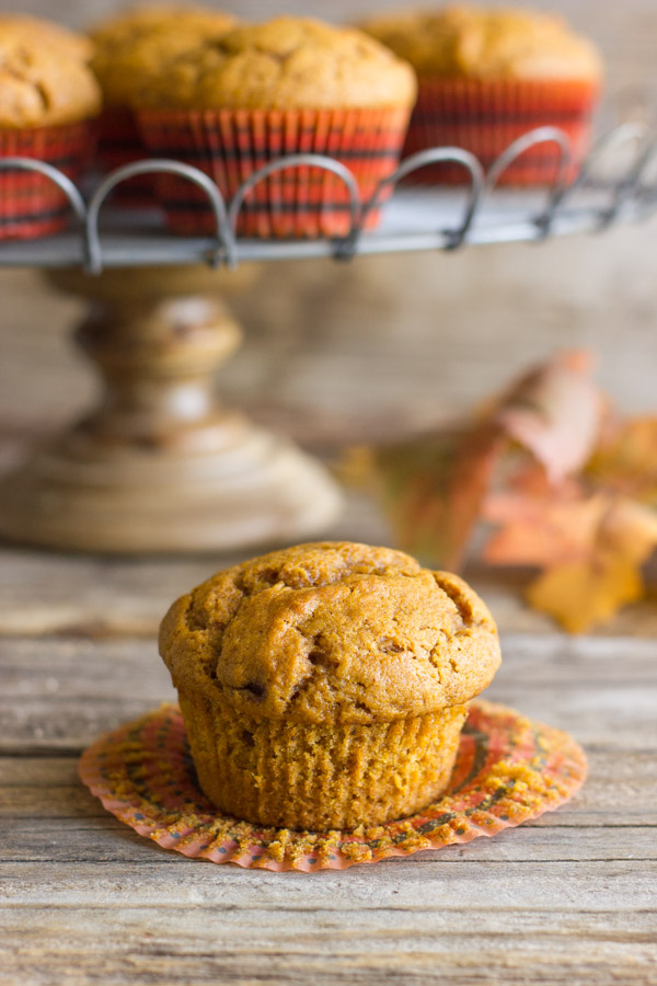 Best Ever Pumpkin Muffin with its wrapper pulled down and more muffins on a metal cake stand in the background.