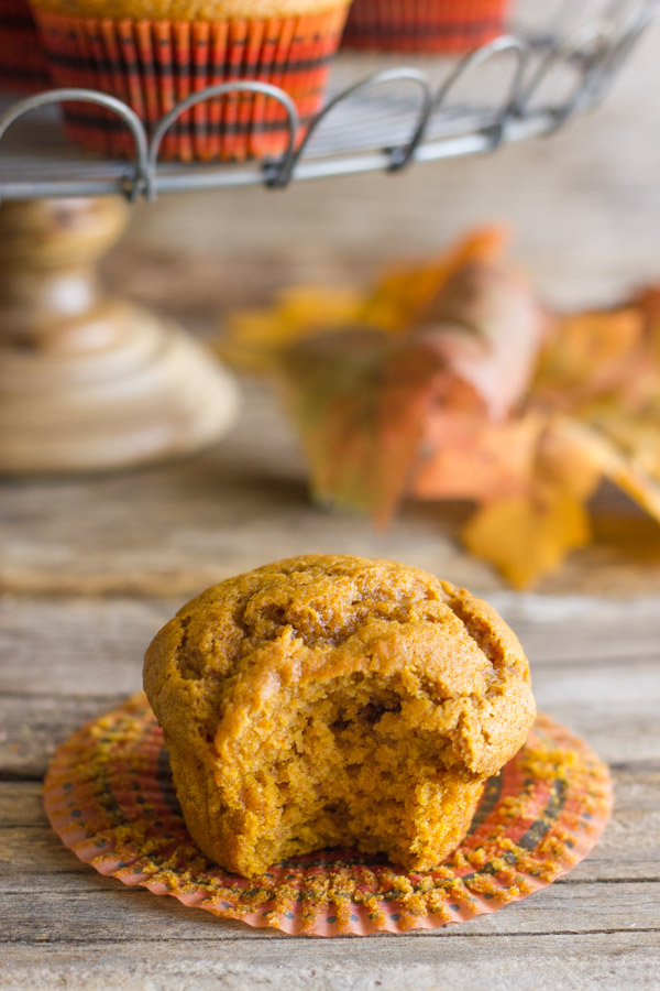 Best Ever Pumpkin Muffin with its wrapper pulled down and a bite taken out of it, with more muffins on a metal cake stand in the background.