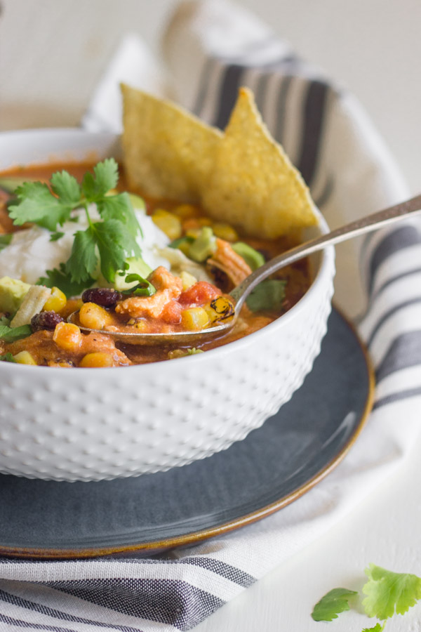 Crockpot Chicken Tortilla Soup in a bowl with a spoon, topped with sour cream, cilantro, diced avocado and tortilla strips, with a few whole tortilla chips dipped in.