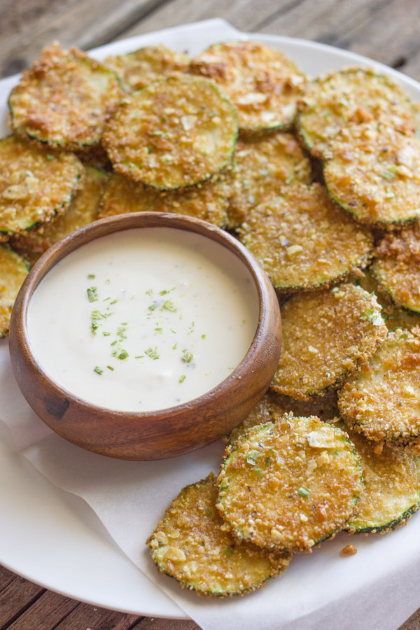 Pita Chip Fried Zucchini on a serving plate with a small bowl of ranch dressing.