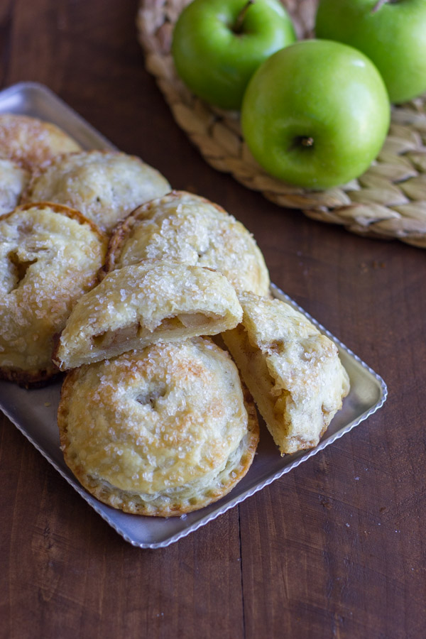 Apple Hand Pies on a serving platter, with one of the Apple Hand Pies cut in half, and some whole apples next to the platter.