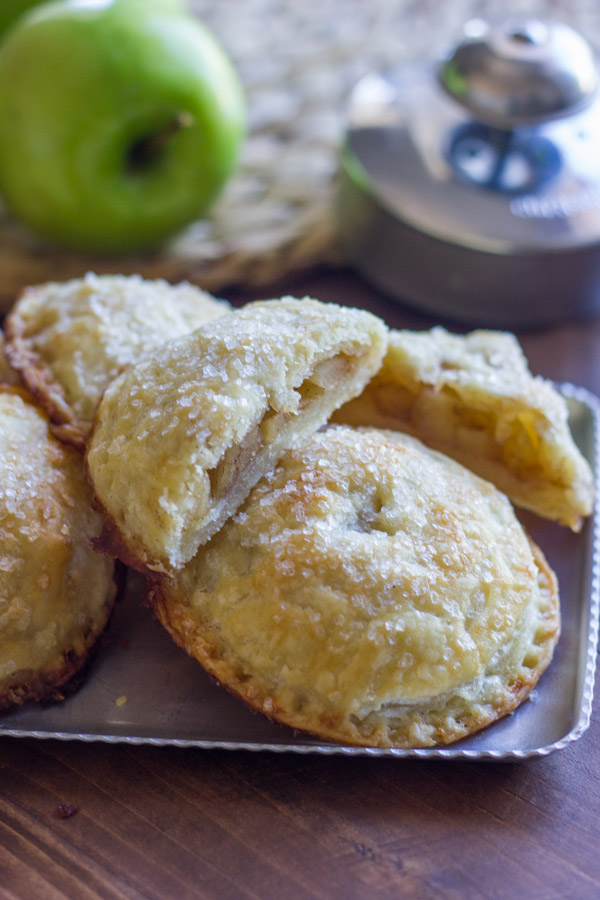 Apple Hand Pies on a serving platter, with one of the Apple Hand Pies cut in half.