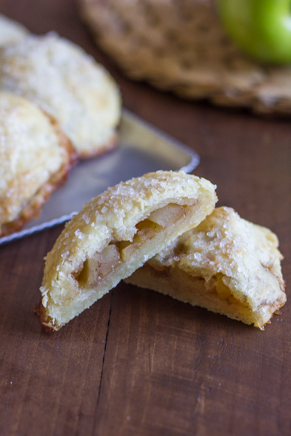 Apple Hand Pie cut in half, with more Apple Hand Pies in the background.