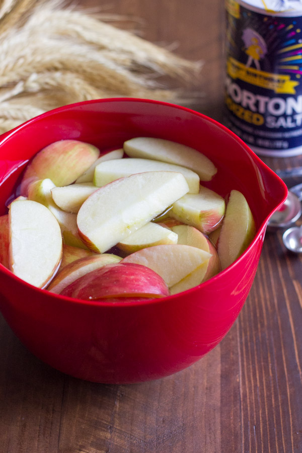 Apple slices soaking in a bowl of salt water.