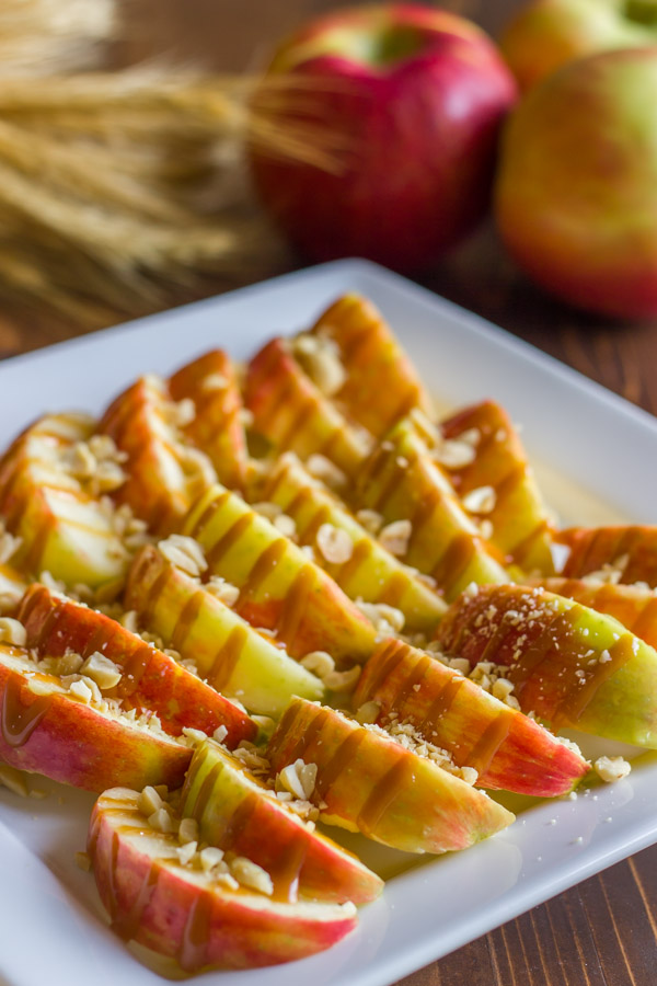 Caramel Apple Slices on a serving platter, with whole apples in the background.