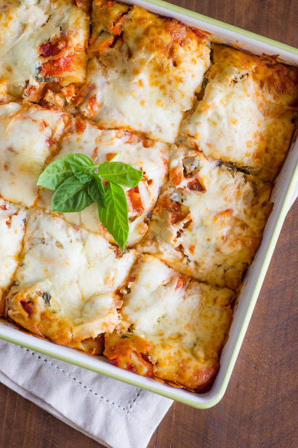 Spinach and Artichoke Chicken Lasagna in a baking dish, sliced into nine square pieces and topped with fresh basil leaves.