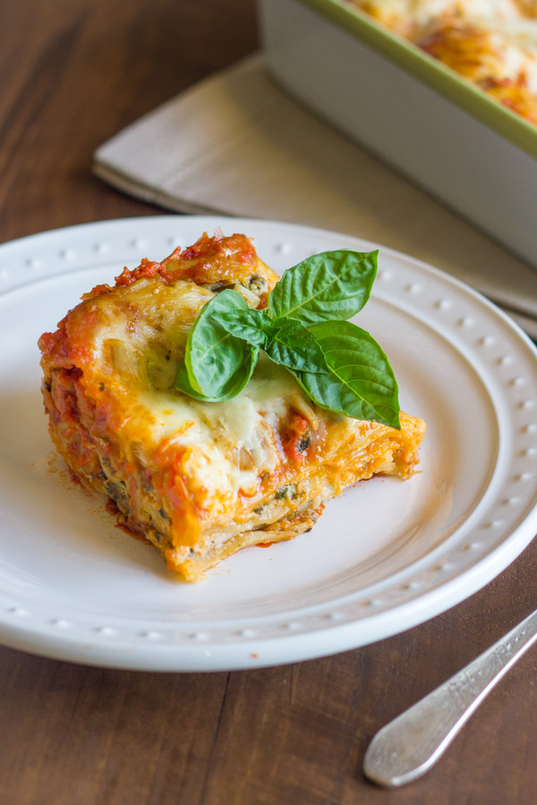 Spinach and Artichoke Chicken Lasagna square piece on a plate, topped with fresh basil leaves.