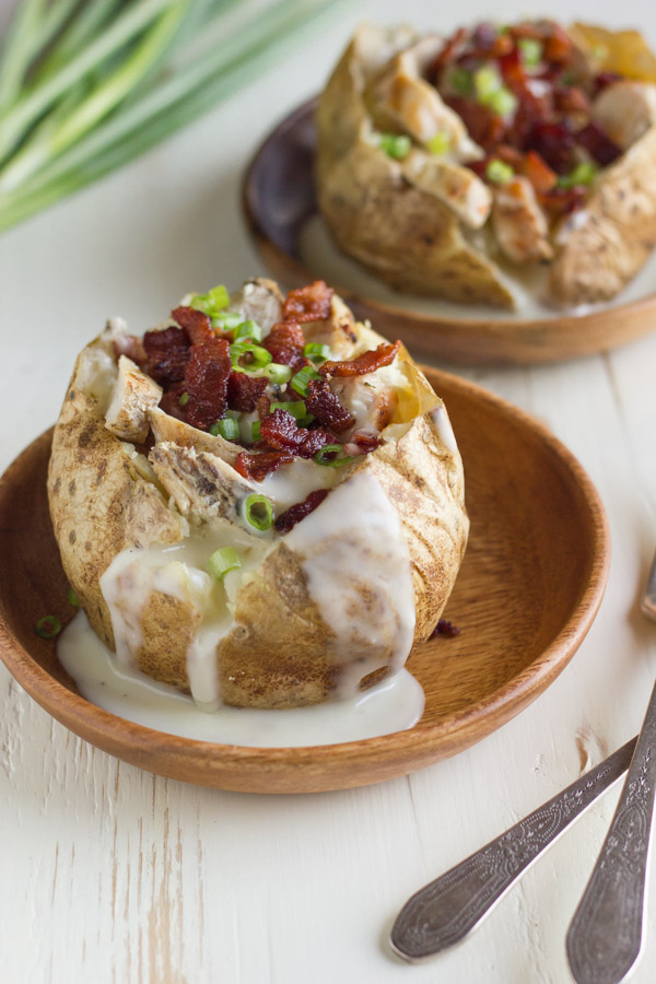 Loaded Chicken and Bacon Alfredo Potatoes on wood plates.