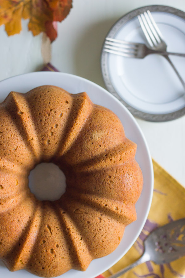 Pumpkin Spice Bundt Cake on a cake stand, with a serving utensil and a plate with forks next to the stand.