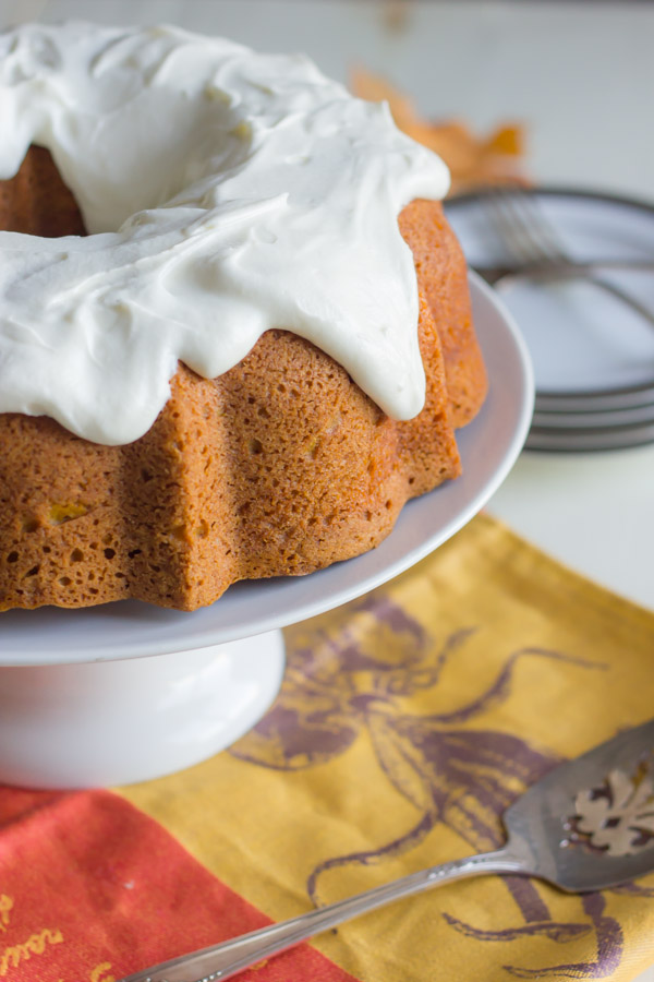 Pumpkin Spice Bundt Cake with frosting on a cake stand, with a serving utensil and a plate with forks next to the stand.