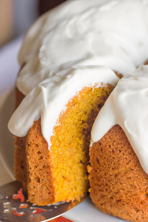A slice of Pumpkin Spice Bundt Cake with frosting on a serving utensil, being pulled away from the rest of the cake.