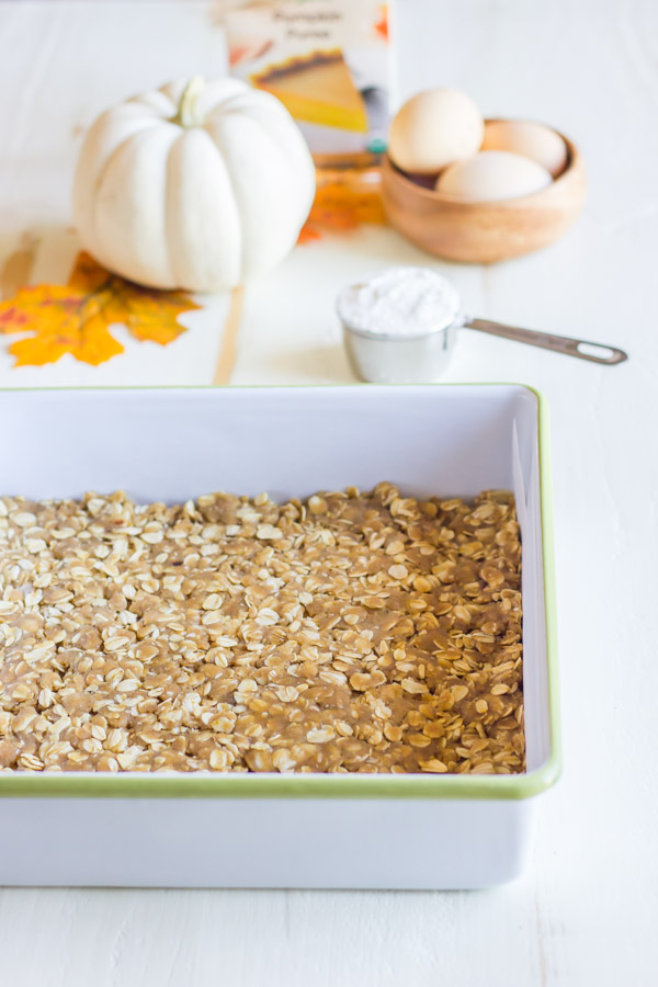 Oatmeal cookie crust for the Pumpkin Pie Cheesecake Bars in a baking dish, with more ingredients in the background.