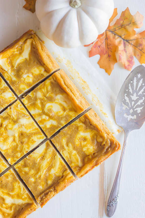 Pumpkin Pie Cheesecake Bars cut into squares, with a serving utensil next to them.