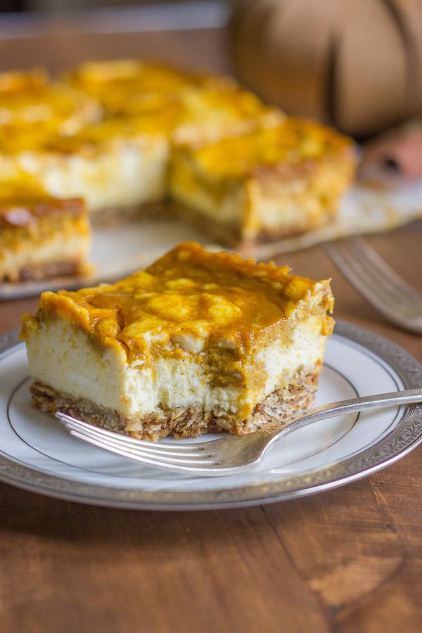 Pumpkin Pie Cheesecake Bar on a plate with a fork, with more Pumpkin Pie Cheesecake Bars in the background.