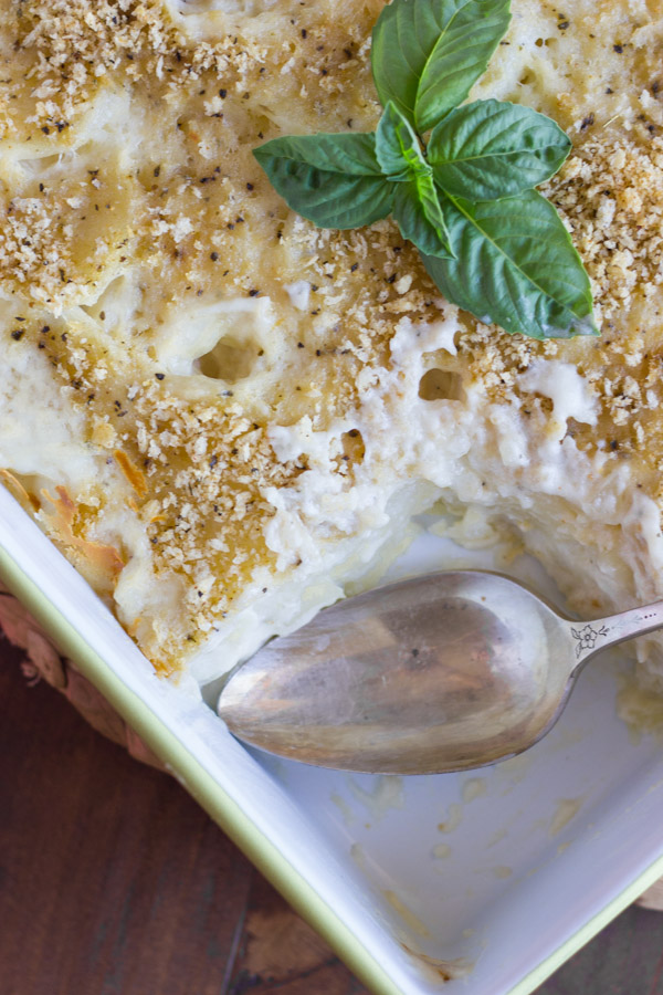 Roasted Garlic Scalloped Potatoes in a baking dish, with a serving spoon in a spot where the potatoes are gone.