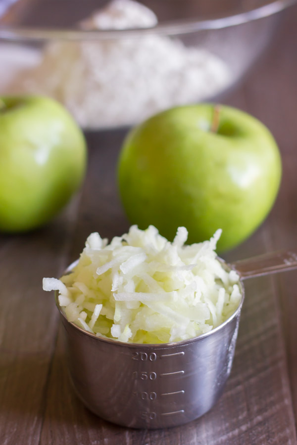 Grated Granny Smith apple in a measuring cup, with whole apples in the background.
