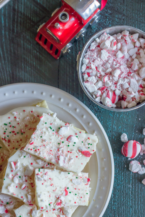Butter Cracker Peppermint Bark piled on a plate, next to a bowl of crushed peppermint candies.