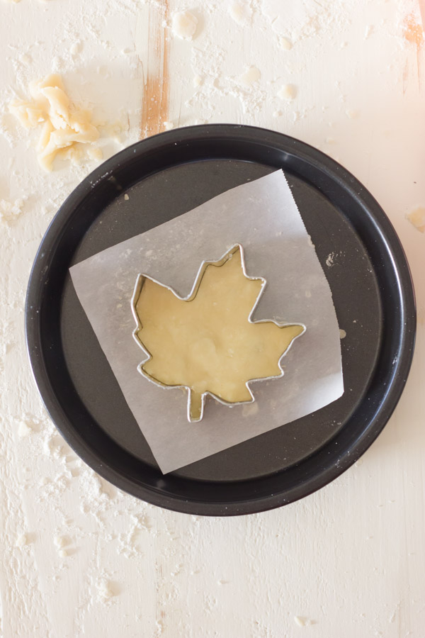 Pie Crust Tutorial Step 7 - leaf shaped cookie cutter with pie dough on parchment paper in a baking pan.