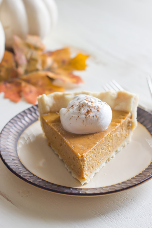 Classic Pumpkin Pie piece on a plate topped with whipped cream.