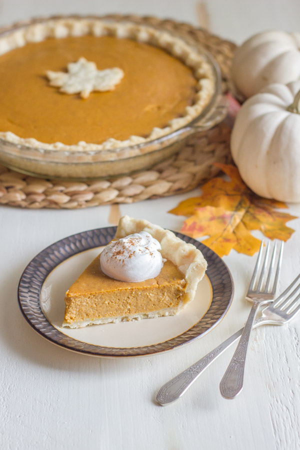 Classic Pumpkin Pie piece on a plate topped with whipped cream, with a whole Classic Pumpkin Pie in the background.