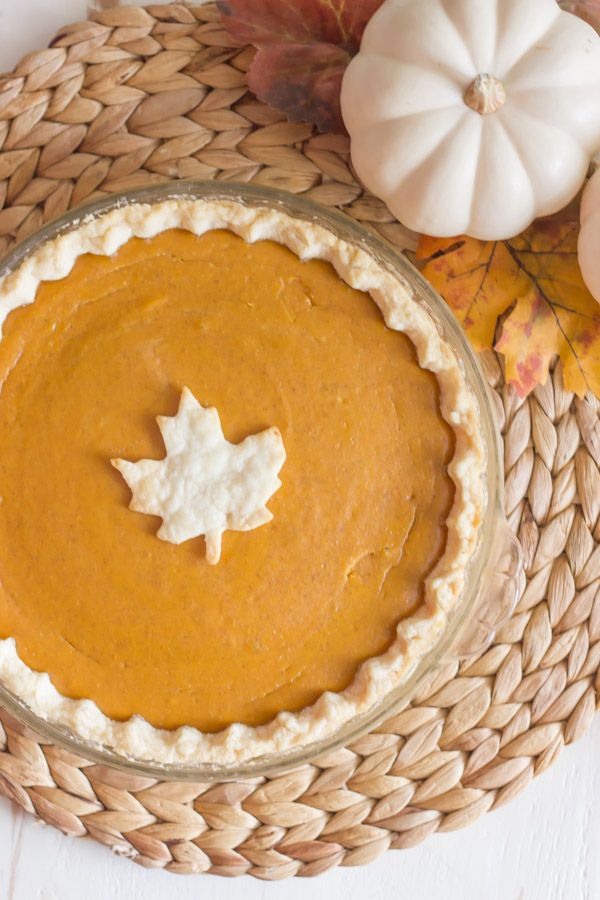 A whole Classic Pumpkin Pie with a leaf decoration, on a placemat with a pumpkin and fall leaves.