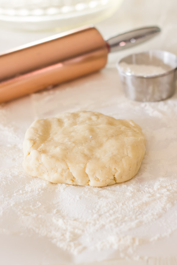 Pie Crust Tutorial Step 4 - pie dough on top of floured parchment paper, with a rolling pin and a cup of flour in the background.