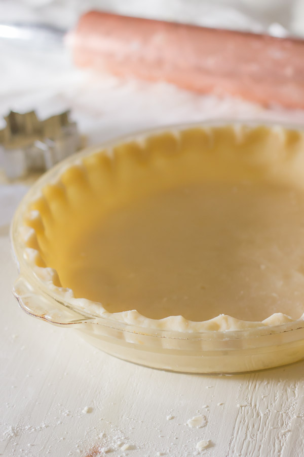 Pie Crust Tutorial Step 7 - pie dough in a pie plate with crimped edges.
