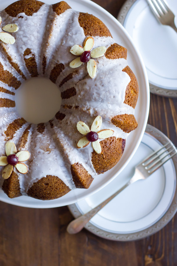 Cranberry Almond Greek Yogurt Cake on a cake stand, with plates and forks next to it.