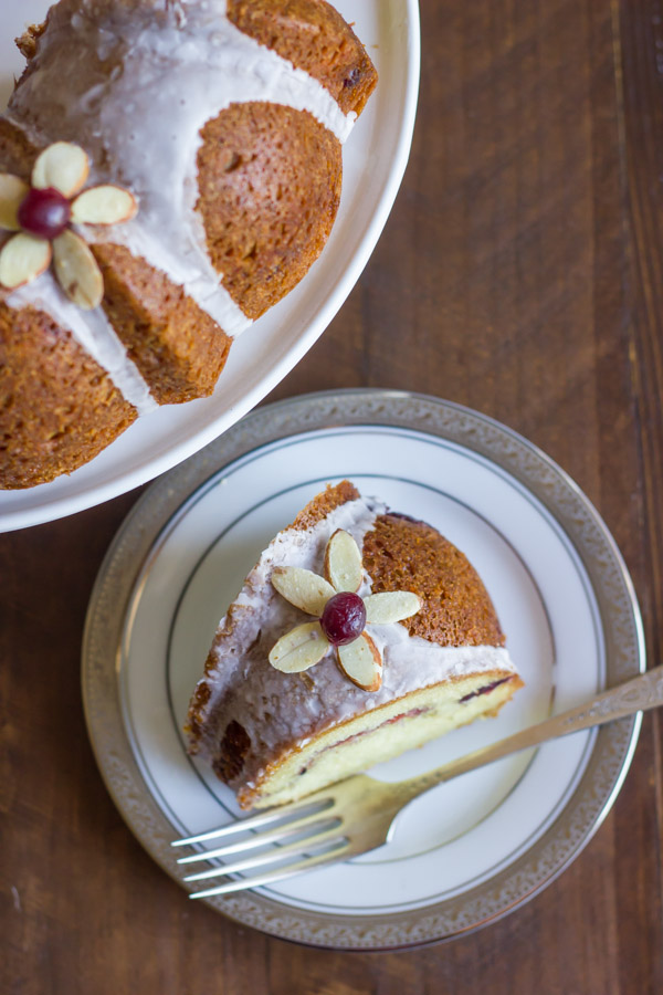 Cranberry Almond Greek Yogurt Cake slice on a plate with a fork, next to the rest of the cake on a cake stand.