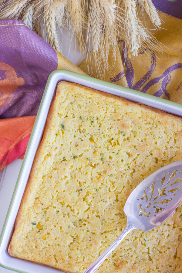 Easy Corn Soufflé in a square baking dish with a serving spoon.