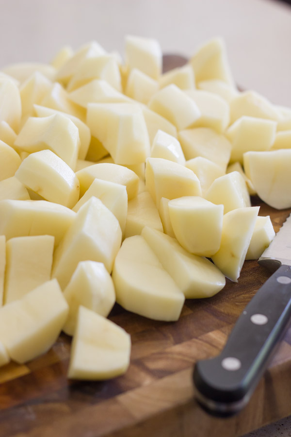Chopped potatoes on a cutting board with a knife.