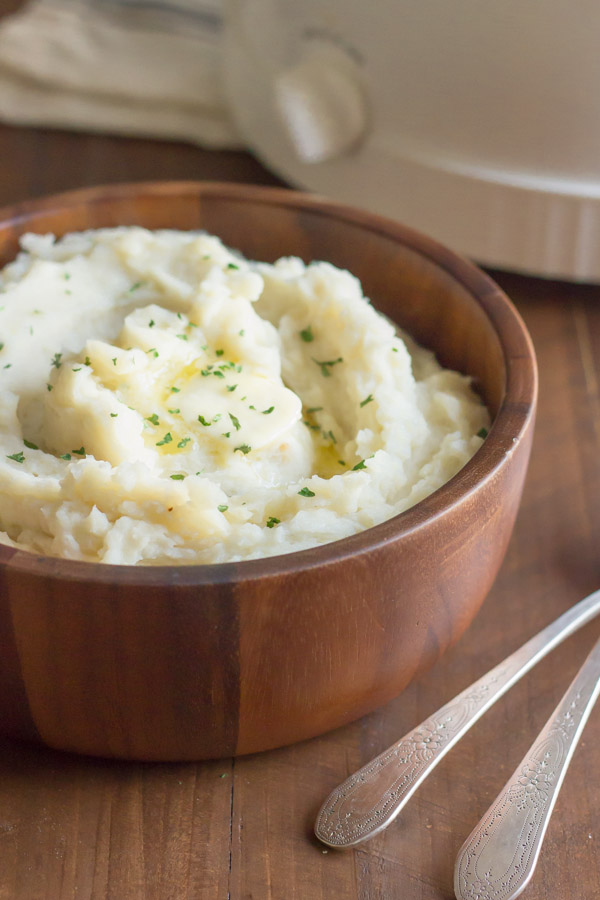 Easy Creamy Crockpot Roasted Garlic Mashed Potatoes in a bowl with butter and dried parsley on top.