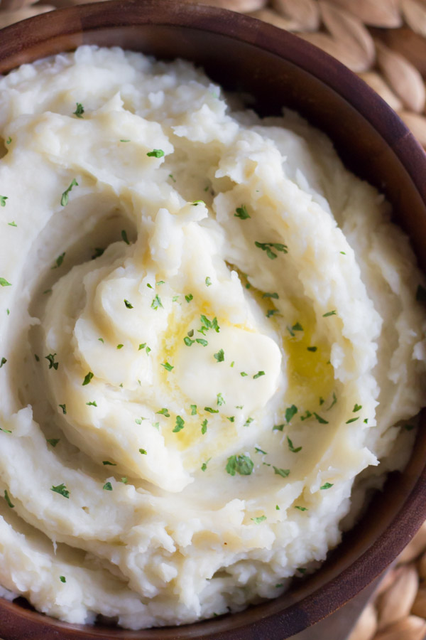 Top down view of Easy Crockpot Mashed potatoes in a wooden serving bowl with a pat of butter on top.