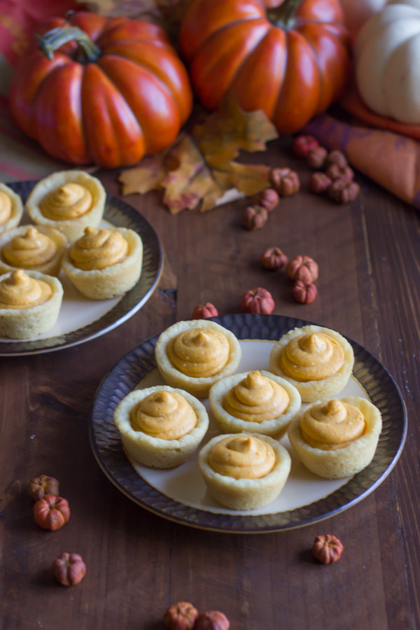 Two plates of Easy Mini Pumpkin Pie Tarts, with fall decorations around them.